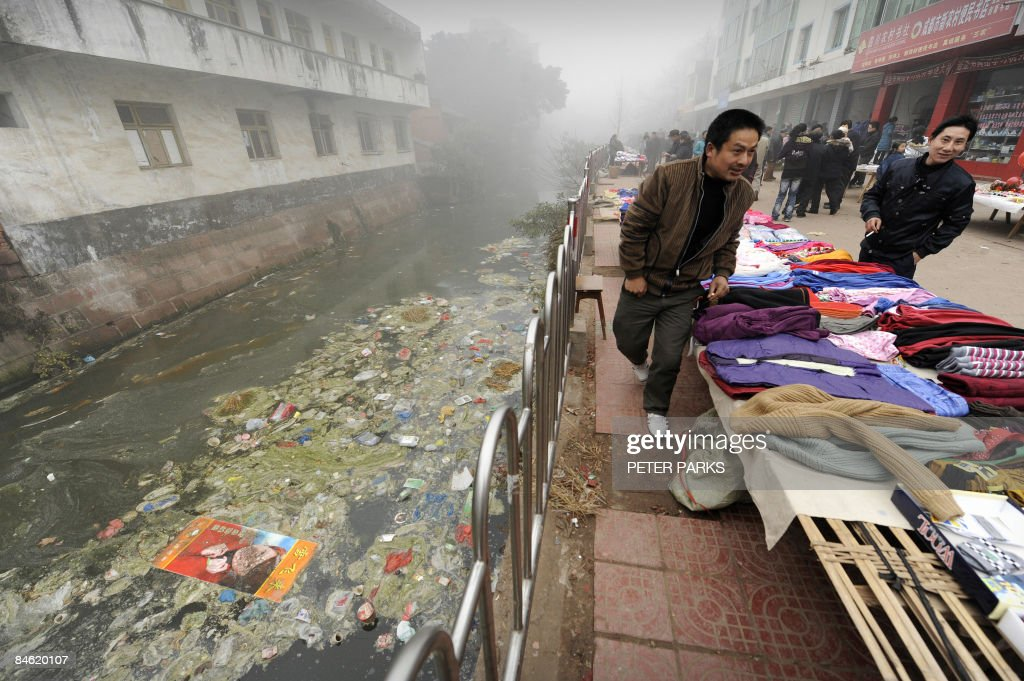 Residents walk by a heavily polluted riv : News Photo