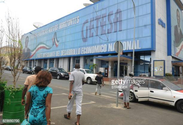 Residents walk by a large electoral banner of Equatorial Guinea incumbent president and candidate Teodoro Obiang in Malabo on April 23 2016 Africa's...