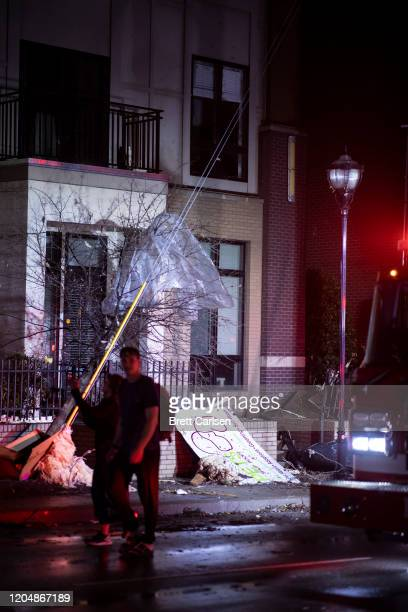 Residents walk by a tornado damaged apartment building on Jefferson St in Nashville TN on March 3 2020 in Nashville Tennessee A tornado passed...