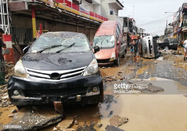 Residents walk by destroyed cars in Bekasi, West Java, on January 2 after flooding triggered by heavy rain hit the area. - Indonesia's disaster...