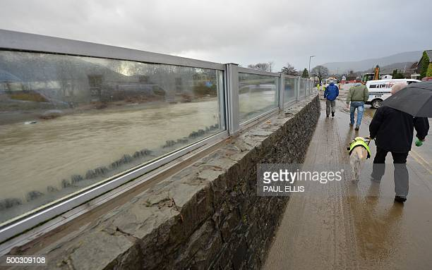 Residents walk by the recently constructed glass flood barrier which failed to stop the rising water in Keswick northern England on December 7 2015...