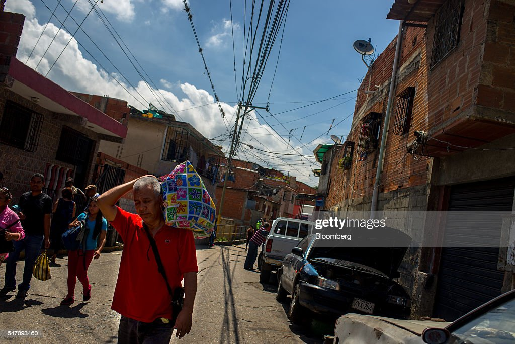 Residents walk down a street of the Catia neighborhood on the outskirts of Caracas, Venezuela, on Saturday, July 2, 2016. In an attempt to regain control, President Nicolas Maduro has tapped loyal neighborhood groups, called Local Committees for Supply and Production (CLAPs), and put them in charge of distributing as much as 70 percent of the nation's food. Photographer: Manaure Quintero/Bloomberg via Getty Images