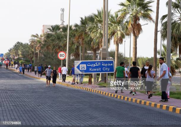 Residents walk in a neighbourhood of Kuwait City on May 12 as authorities allowed people to exercise for two hours under a nationwide lockdown due to...