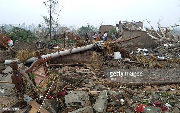 Residents walk in the rubble of destroyed houses after a tornado in Funing in Yancheng in China's Jiangsu province on June 23 2016 xtreme weather...