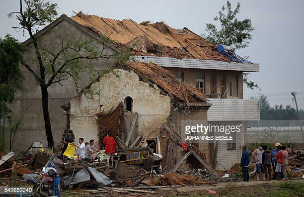 TOPSHOT Residents walk in the rubble of destroyed houses after a tornado in Funing in Yancheng in China's Jiangsu province on June 24 2016 Extreme...