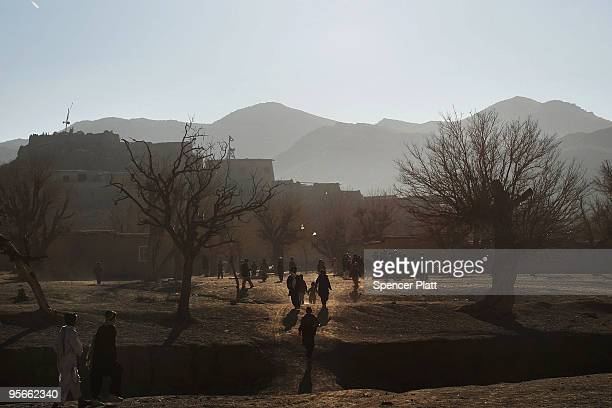 Residents walk in the village of Pushtay where a US Army Provincial Reconstruction Team made a visit on January 9, 2010 in Pushtay, Afghanistan....