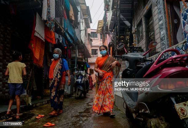 Residents walk inside the Dharavi slum in Mumbai on August 11, 2020.