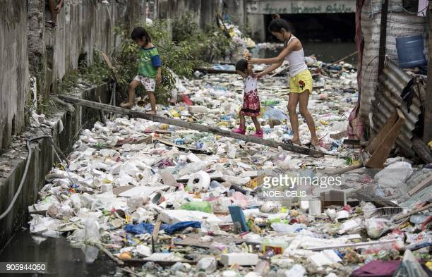 Residents walk on a wooden plank to cross a garbagefilled waterway in Manila on January 17 2018 / AFP PHOTO / NOEL CELIS