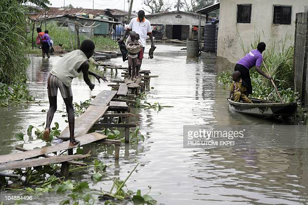 Residents walk on makeshift narrow footpath leading to their flooded home at Ajegunle, Ikorodu Road, in Lagos on October 6, 2010. Thousands of people...