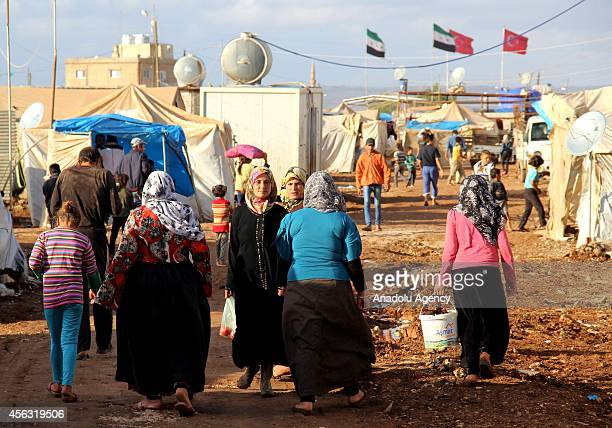 Residents walk on muddy road at the tent city close to Al Salama border gate in Azez district of Aleppo, Syria on September 29, 2014.