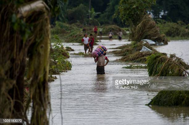 Residents walk on road submerged by flood waters from Swar Chaung Dam in Swar township in Bago region on August 30 2018 Swar Chaung dam's spillway...