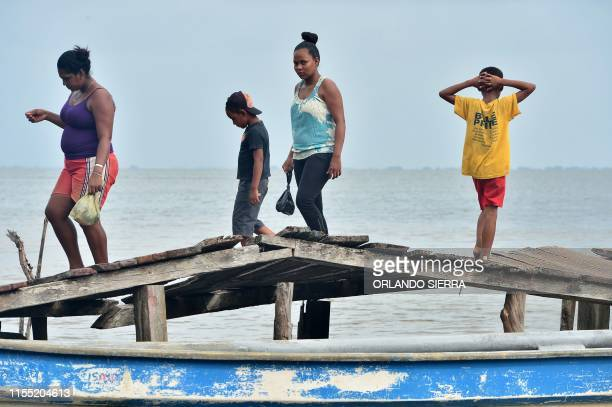 Residents walk over a damaged wood dock on the shore of Prumnitara Puerto Lempira Honduras on July 8 2019 Thousands of fishing divers of the...