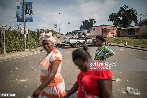 Residents walk past a burned barricade in Libreville on September 1 2016 The results of the presidential election announced earlier on August 31 2016...