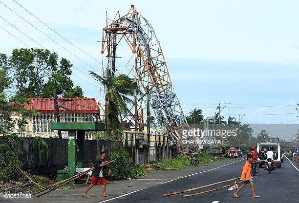Residents walk past a downed cell network tower in Polangui Albay province on December 26 2016 Typhoon NockTen which made landfall on the eastern...