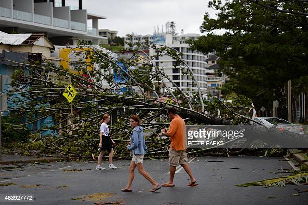 Residents walk past a fallen tree brought down by Tropical Cyclone Marcia in the northern Queensland town of Yeppoon on February 20 2015 Two powerful...