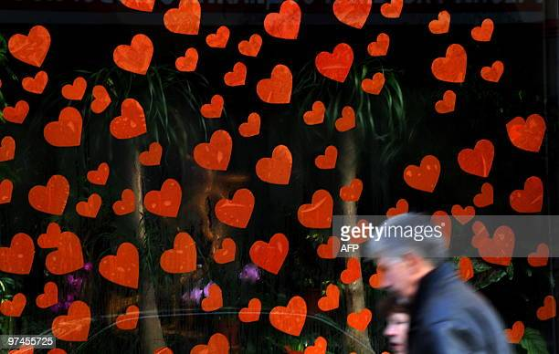 Residents walk past a flower market decorated with hearts a day before St Valentine's Day in central Sofia on February 13 2010 Valentine's Day named...