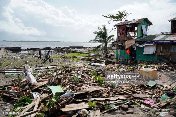 TOPSHOT Residents walk past a house damaged during Typhoon Phanfone in Tacloban Leyte province in the central Philippines on December 25 2019 Typhoon...