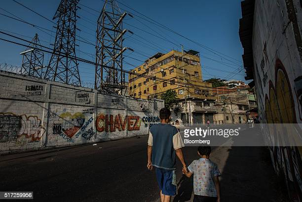 Residents walk past an electrical substation run by Corpoelec a state power corporation in the Catia slum regularly subject to statemandated...