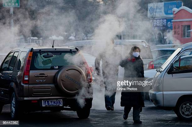 Residents walk past automobile exhaust on a road on December 28 2009 in Changchun of Jilin Province China According to state media China has pledged...