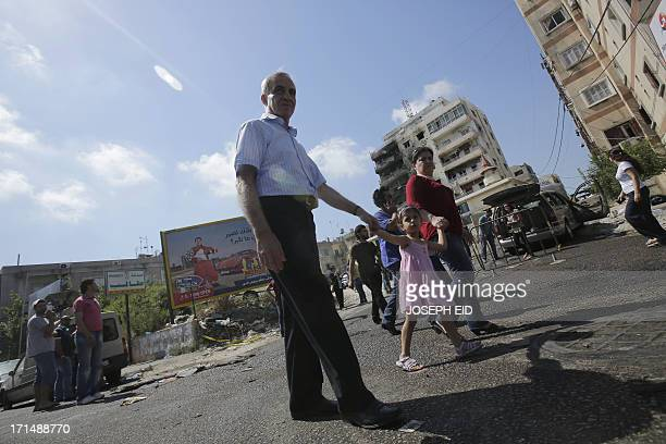 Residents walk past Bilal bin Rabah mosque following clashes between the Lebanese army and supporters of radical Sunni cleric Sheikh Ahmad alAssir in...