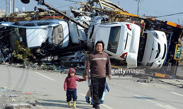 Residents walk past cars upturned by the tsunami to the east of Sendai in Miyagi prefecture on March 13 2011 two days after a massive 89 magnitude...
