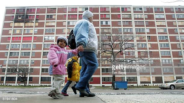Residents walk past one of the few remaining Chicago Housing Authority CabriniGreen public housing buildings January 12 2005 in Chicago Illinois The...