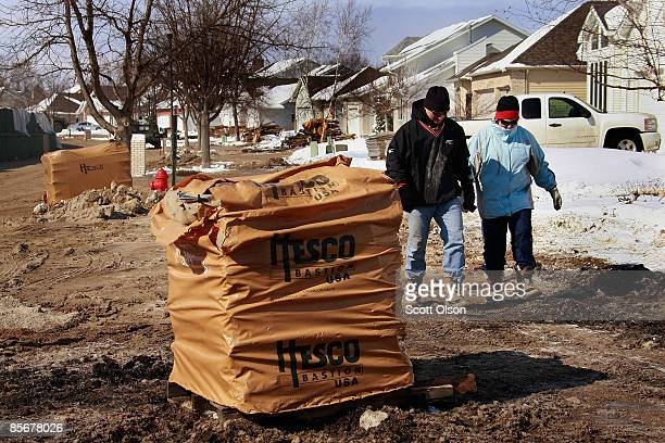 Residents walk past pallets of Hesco barriers being used to build levees to hold back flood water from the Red River March 28 2009 in Fargo North...