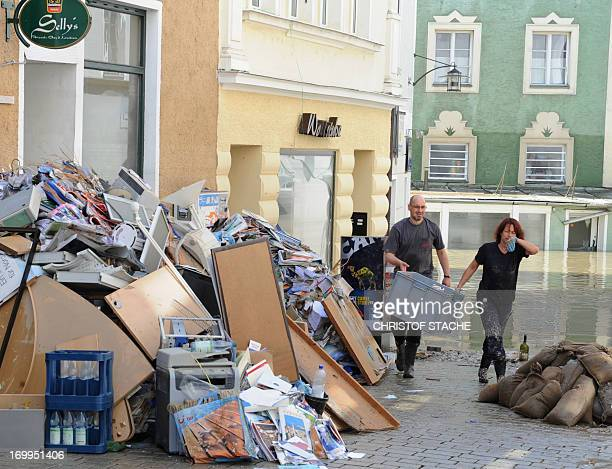 Residents walk past sandbags and rubbish piled up in a street flooded by the river Danube in Passau southern Germany on June 5 2013 German Chancellor...