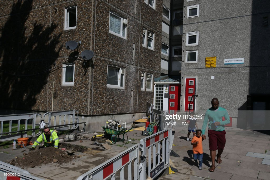Residents walk past Southern Gas Network employees at work on Ledbury estate in Peckham, south-east London on August 11, 2017. Residents of the Ledbury estate in Peckham, south-east London face evacuation as four tower blocks are at risk of collapse in the event of a gas explosion, with the gas supply to Ledbury Towers cut off on August 11. / AFP PHOTO / Daniel LEAL