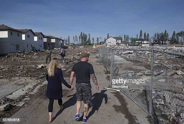 Residents walk past the remains of homes destroyed by wildfire in the Timberlea neighborhood of Fort McMurray Alberta Canada on Thursday June 2 2016...