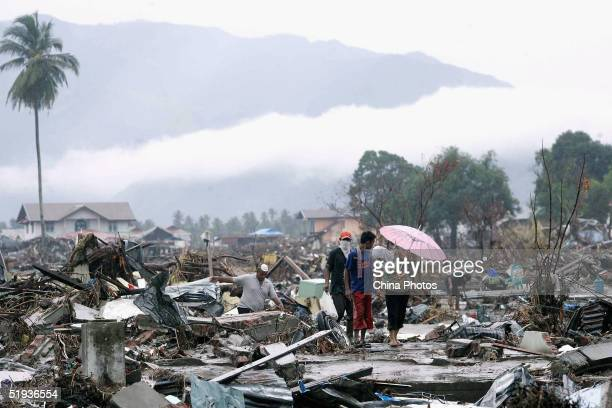 Residents walk past the ruins of their downtown homes January 10 2005 in Banda Aceh Indonesia The death toll from the earthquake and tsunami in...