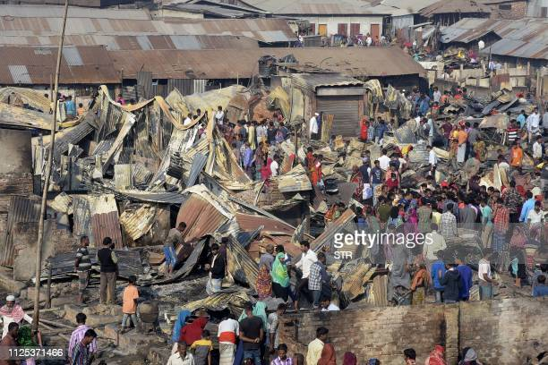 TOPSHOT Residents walk past their destroyed houses after a fire broke out in Chittagong on February 17 2019 A fire tore through a slum in southern...