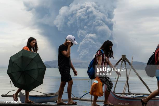 Residents walk past wooden boats as Taal volcano erupts in Tanauan town Batangas province south of Manila on January 13 2020 Lava and broad columns...