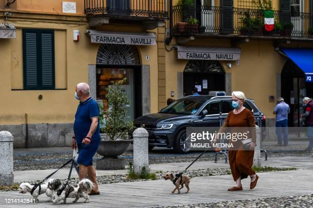 Residents walk their dogs on May 20, 2020 in Codogno, southeast of Milan, one of the villages at the epicenter of the coronavirus epidemic in...