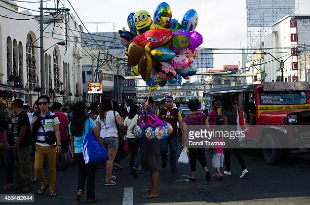 Residents walk through a downtown market area as a man sells ballons on August 11 2014 in Manila Philippines The Philippines has one of the fastest...