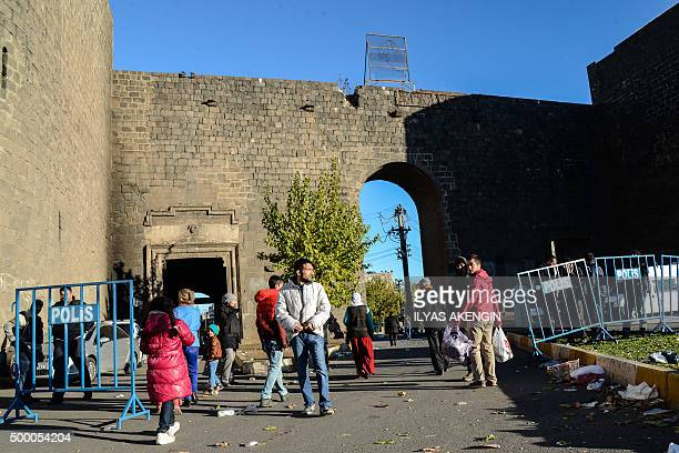 Residents walk through a police barricade in Diyarbakir's historical Sur district, which has been placed under a curfew, on December 5, 2015. More...