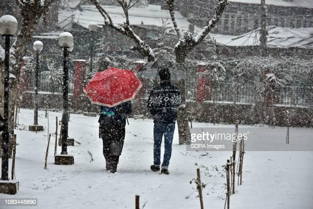 Residents walk through a snow covered park during heavy snowfall in Srinagar Indian administered Kashmir Fresh snowfall began in Kashmir valley...