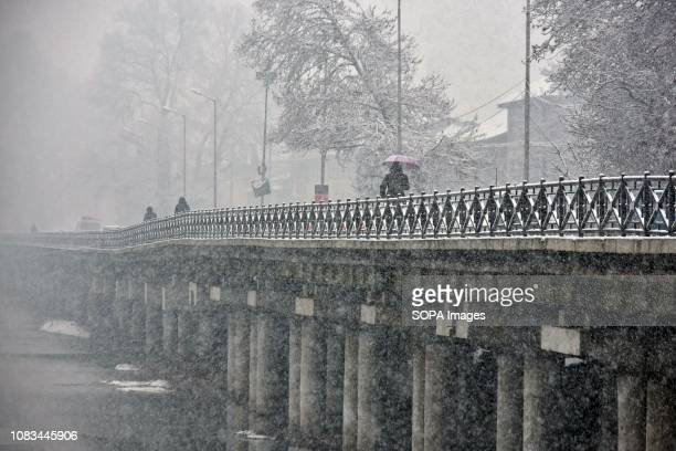 Residents walk through a street during heavy snowfall in Srinagar Indian administered Kashmir Fresh snowfall began in Kashmir valley breaking the...