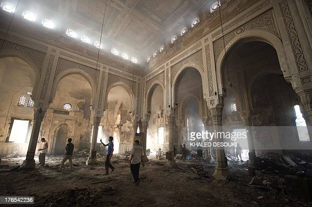 Residents walk through debris and rubble inside the burnt down mosque of Rabaa alAdawiya on August 15 2013 in Cairo Egypt Islamists vowed to rally...