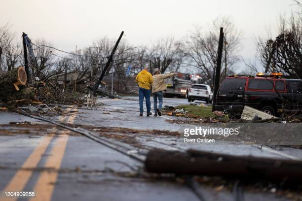 Residents walk through downed utility lines and trees to survey damage caused by one of several tornadoes that tore through the state overnight on...