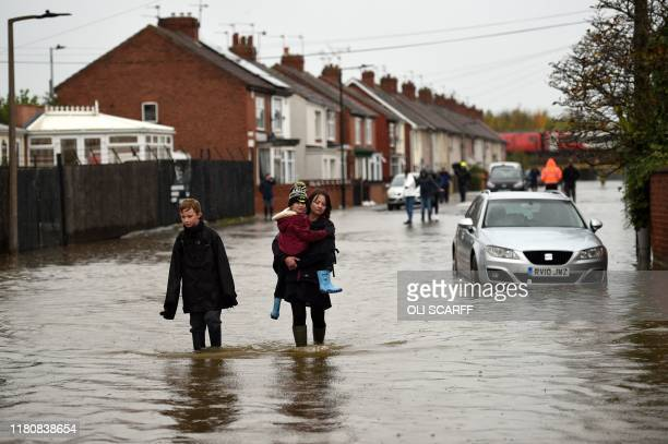 Residents walk through floodwater in Doncaster, northern England on November 8 following flash flooding the previous day. - Over a month's worth of...