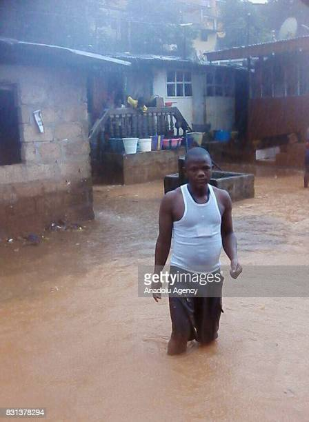 Residents walk through floodwaters in an area of Freetown after landslides struck the capital of the west African state of Sierra Leone on August 14...