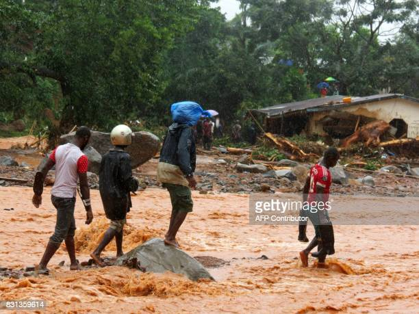 Residents walk through floodwaters past a damaged building in an area of Freetown on August 14 after landslides struck the capital of the west...