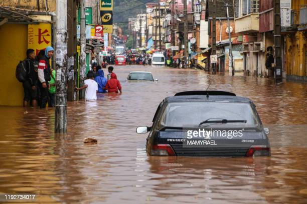 Residents walk through floodwaters past submerged vehicles on a road in Antananarivo on January 8 after heavy rainfall.