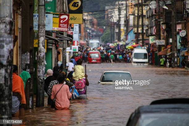 TOPSHOT Residents walk through floodwaters past submerged vehicles on a road in Antananarivo on January 8 after heavy rainfall