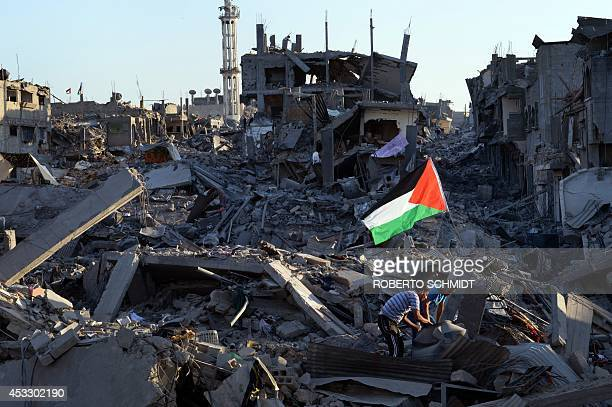 Residents walk through the rubble of his destroyed home as a Palestinian flag flutters in the wind in the devastated neighbourhood of Shejaiya in...