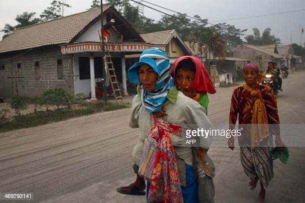 Residents walk to an evacuation center along the ash covered road of Kediri in East Java province following the eruption of Mount Kelud volcano on...