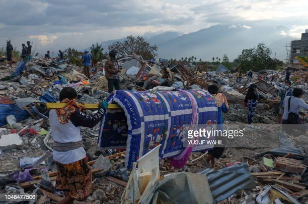 Residents walk trough debris in Petobo Indonesia's Central Sulawesi on October 6 following the September 28 earthquake and tsunami The city of Palu...