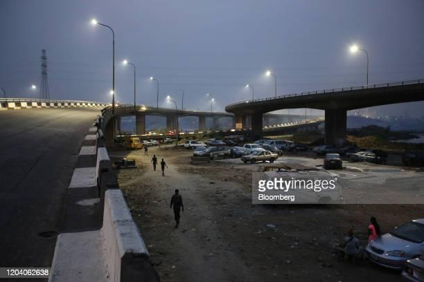 Residents walk under a road bridge as night falls in Lagos, Nigeria, on Friday, Feb. 28, 2020. Nigerian health authorities said theyre tracing...