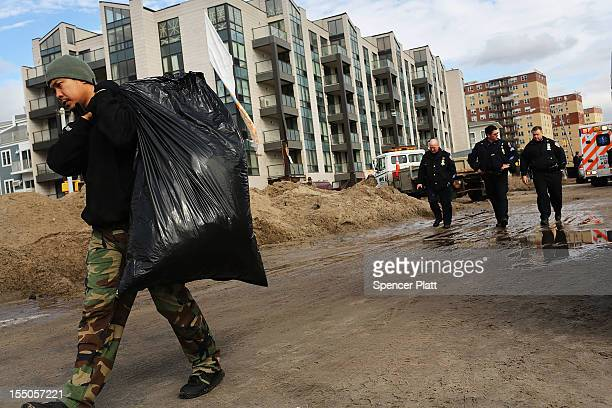 Residents walk with their belonglings through the heavily damaged Rockaway section of Queens where part of the historic boardwalk was washed away due...